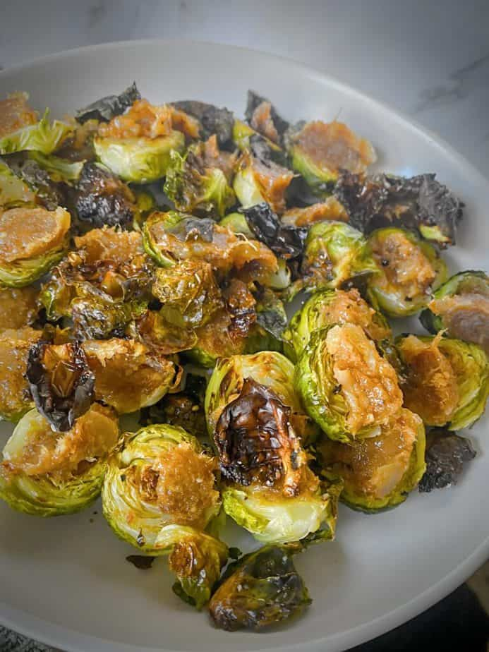 bacon jam topped roasted brussels sprouts steaming on a white plate
