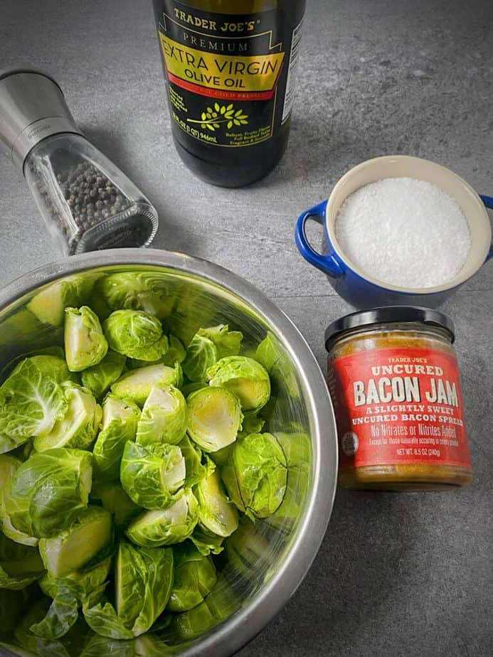 halved fresh brussels sprouts in a silver bowl with a jar of trader joe's bacon jam, kosher salt in a blue salt cellar, a bottle of olive oil and a pepper grinder.