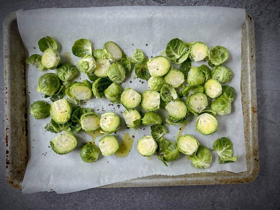 halved brussels sprouts on a parchment lined sheet pan