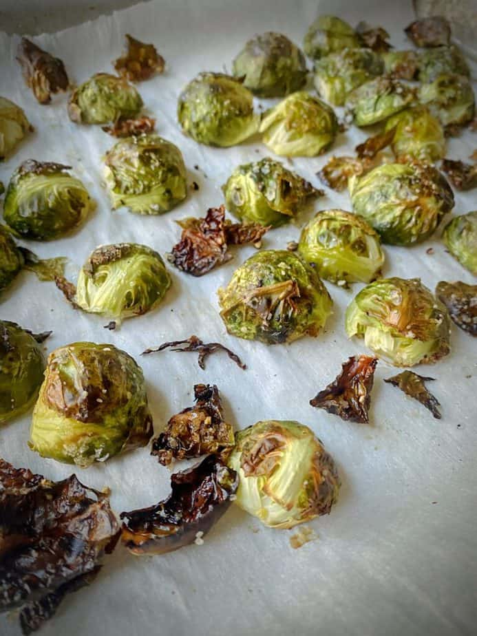browned and roasted brussels sprouts on a piece of parchment paper
