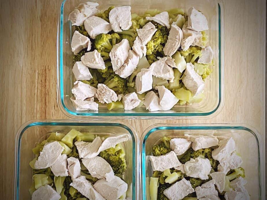 cubed chicken breast layered over broccoli in a trio of small casserole dishes