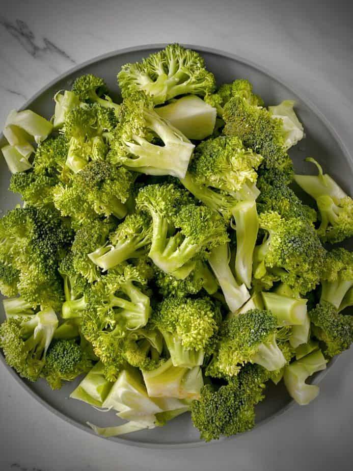 fresh broccoli florets on a light grey plate