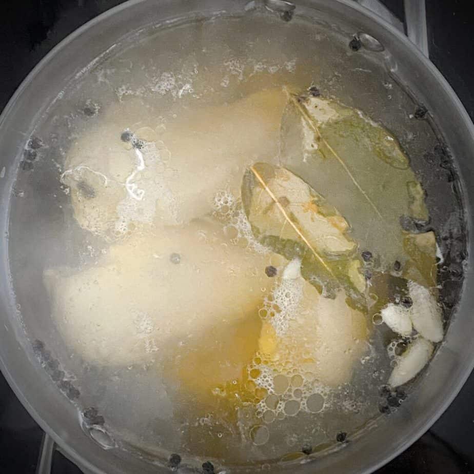 chicken poaching in seasoned liquid