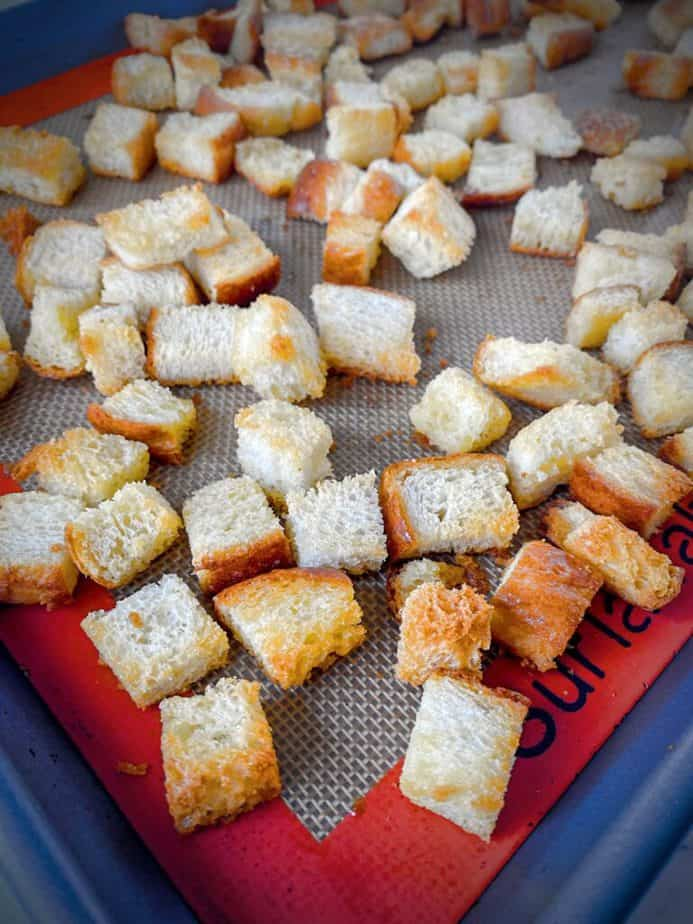 homemade baked croutons after baking on a silpat lined baking sheet