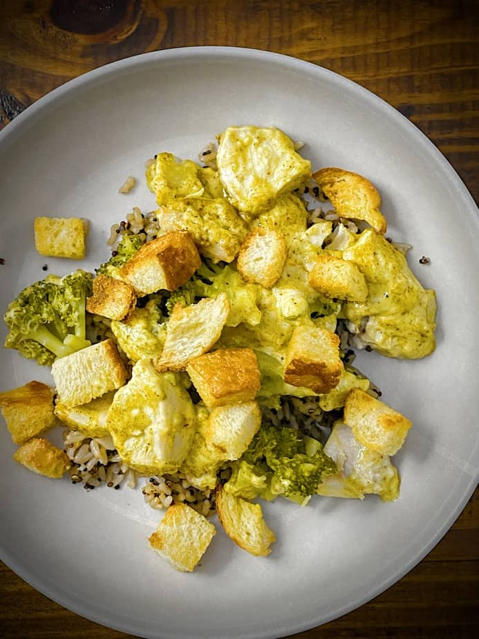 overhead shot of chicken divan casserole in a grey pasta bowl over heap of jasmine rice