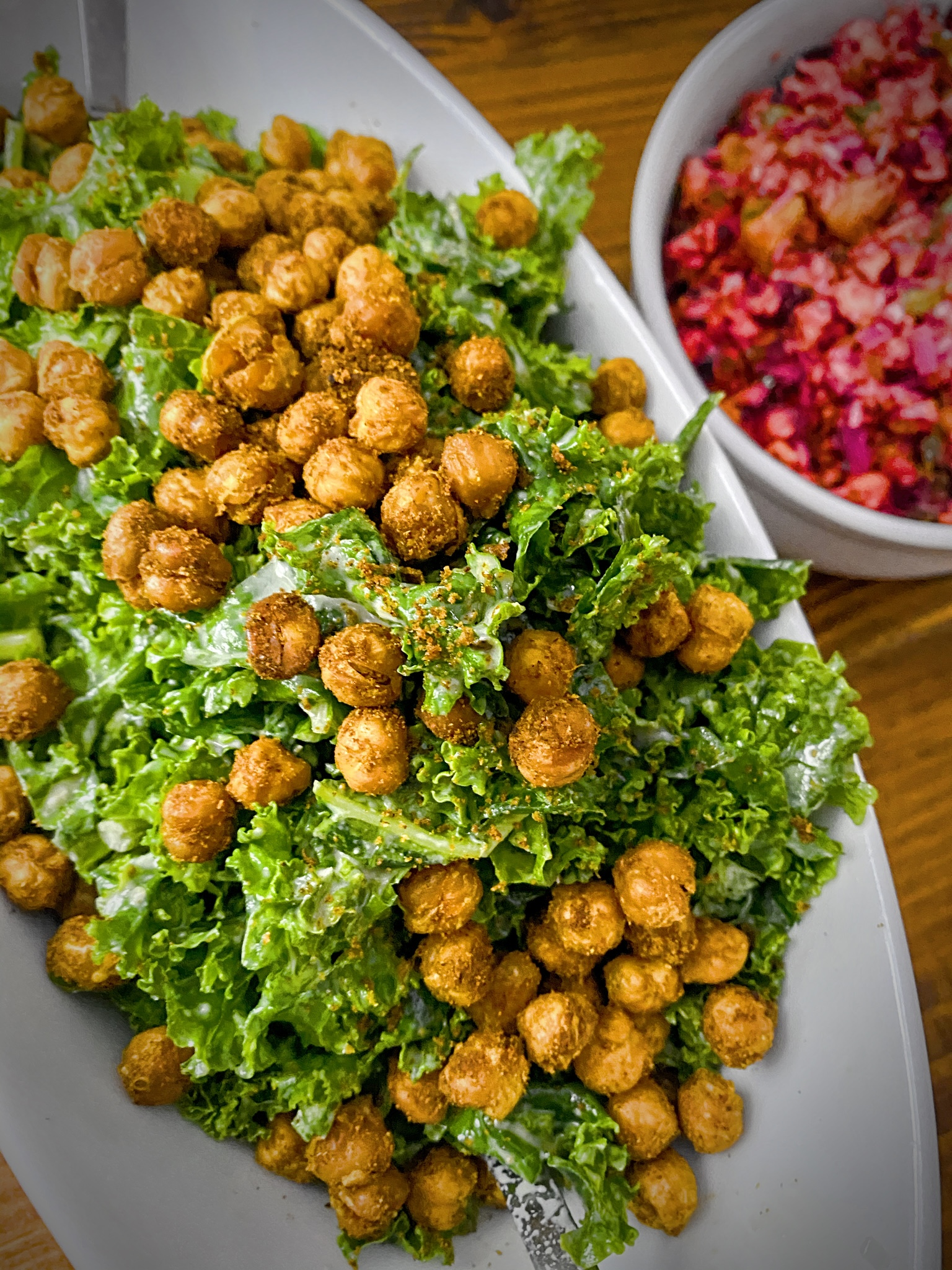 kale salad with tandoori roasted chickpeas in an oblong white dish on a wooden table with a bowl of cranberry relish to the side