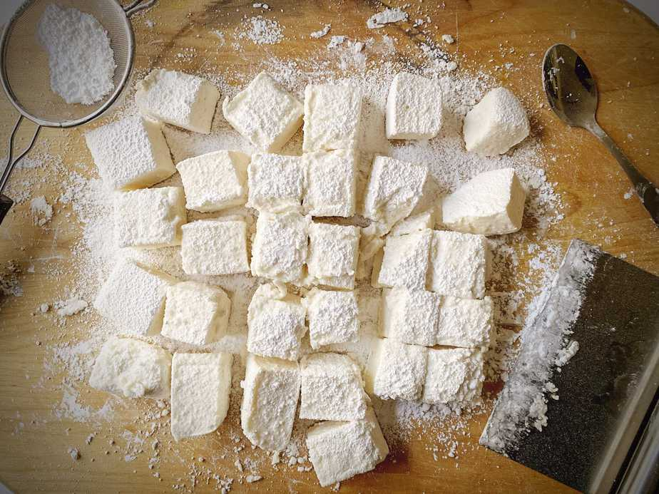 Marshmallows tossed in powdered sugar and corn starch on a wooden cutting board after being cut by a bench scraper