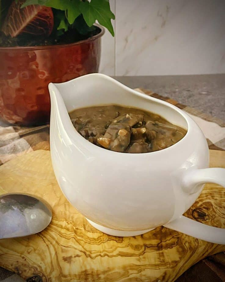 close up shot of mushroom gravy in a white gravy boat on an olive wood board with a copper planter filled with an autumn arrangement behind it