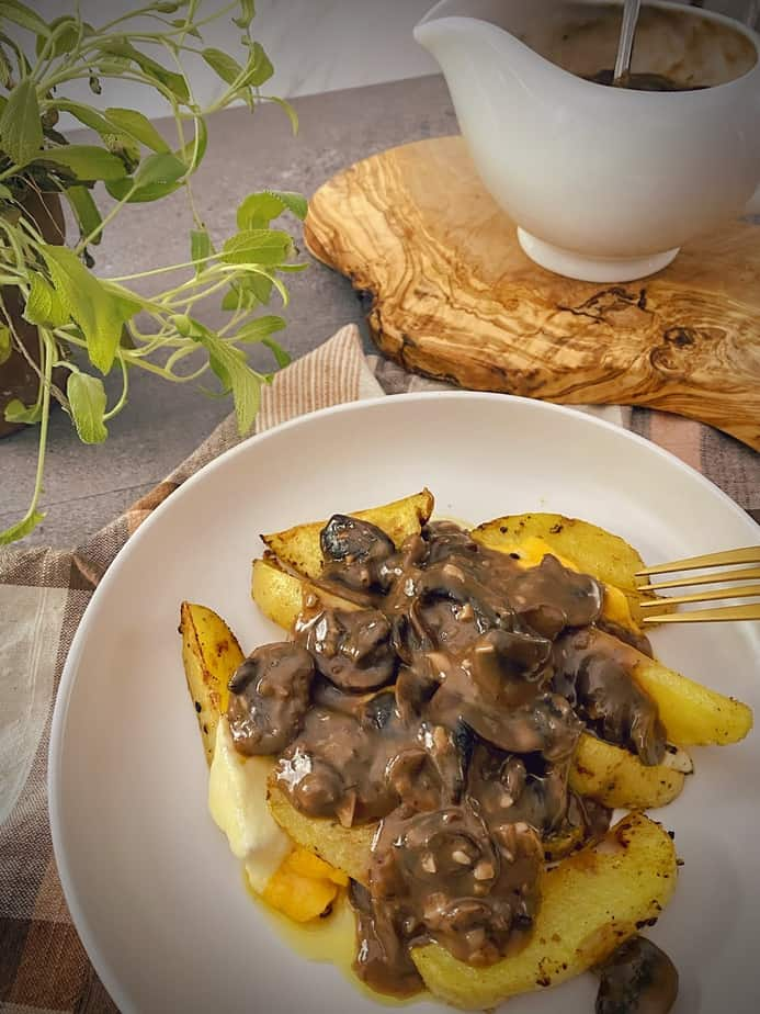 poutine with mushroom gravy in a white pasta bowl with a gravy boat and a sage plant