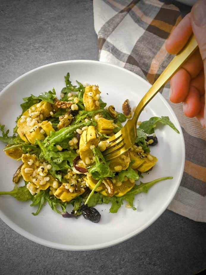 hand holding a gold fork with a bite of roasted delicata squash salad above a white pasta dish and a brown, white and pale orange plaid napkin