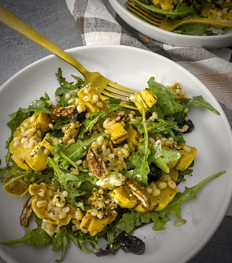 white pasta bowl filled with roasted delicata squash fall salad with a gold fork on a grey table