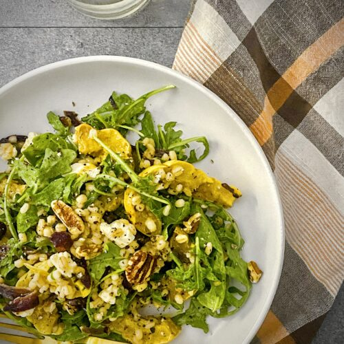 overhead shot of delicata squash harvest salad in a white pasta bowl with a pale orange, brown and white plaid napkin and a glass of white wine