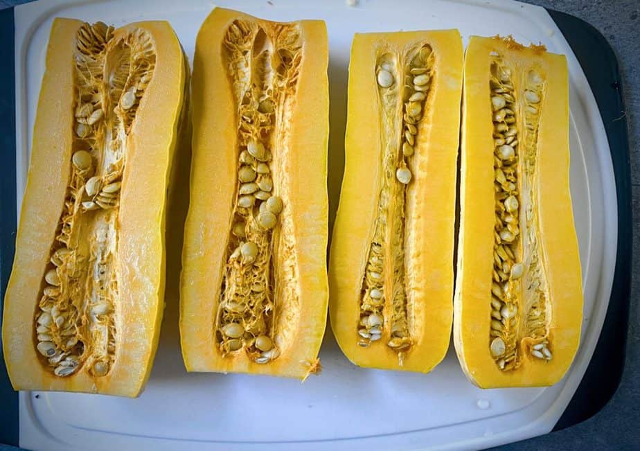 two delicata squash that have had the ends removed and have been cut in half vertically on a white cutting board