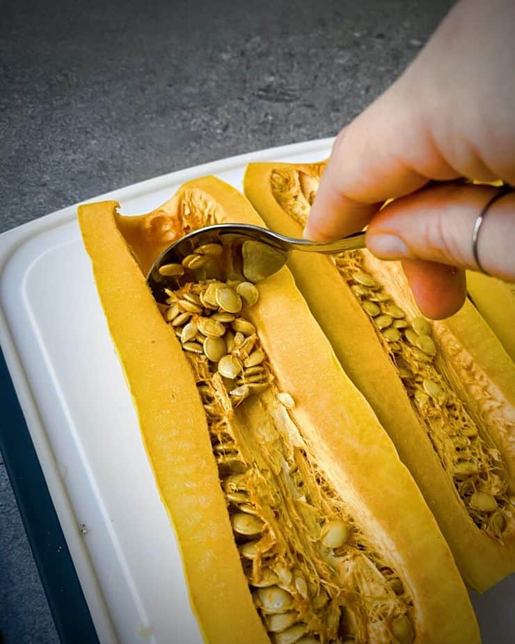 hand holding a silver spoon that is scraping out the seeds of a delicata squash