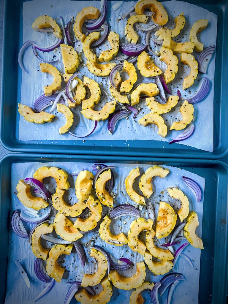 slices of delicata squash and red onions that have been seasoned and placed on parchment lined sheet pans for roasting