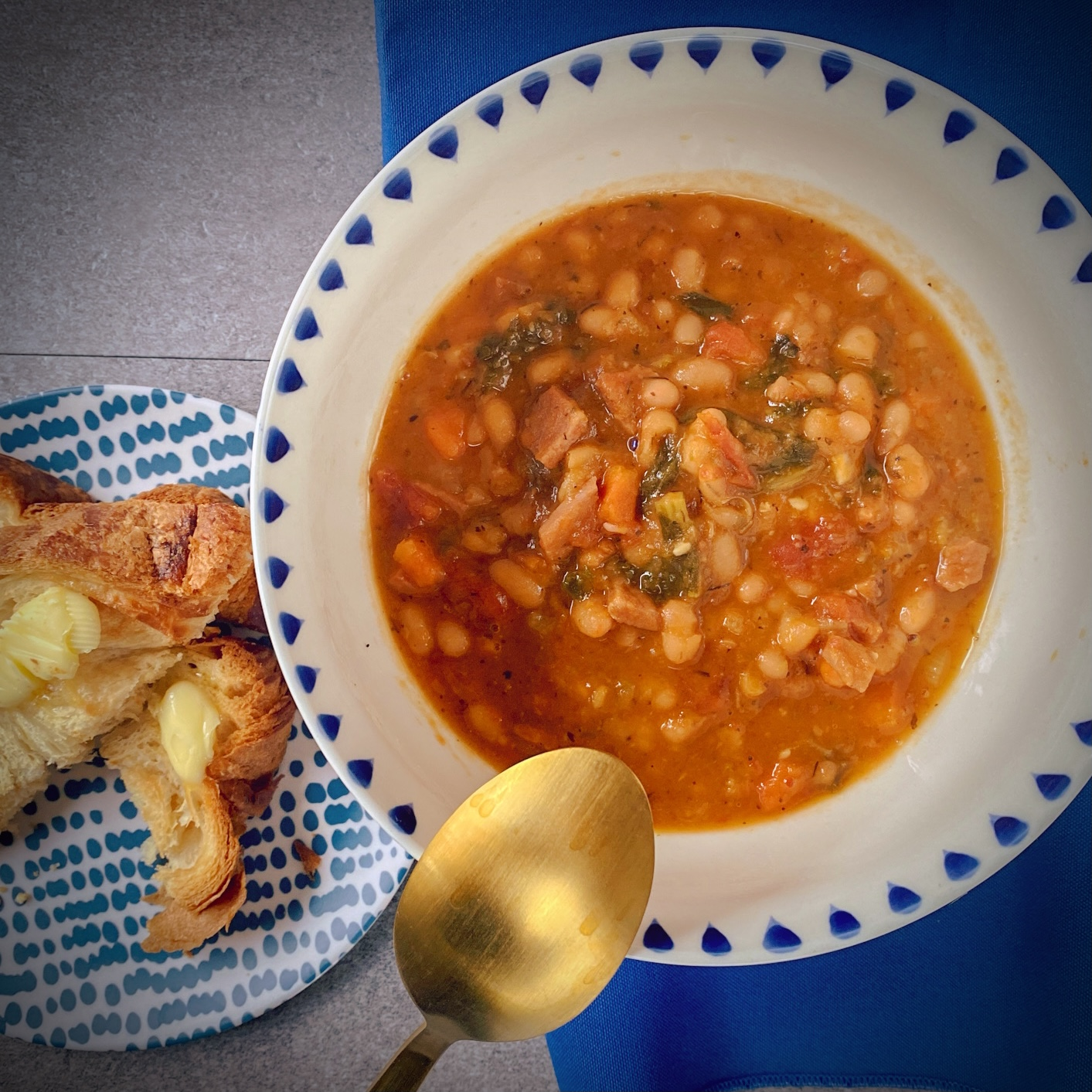 Instant Pot Navy Bean Soup with tomatoes, kale and ham in a white soup bowl with a blue border and some buttered croissant toast on a navy and white dotted plate