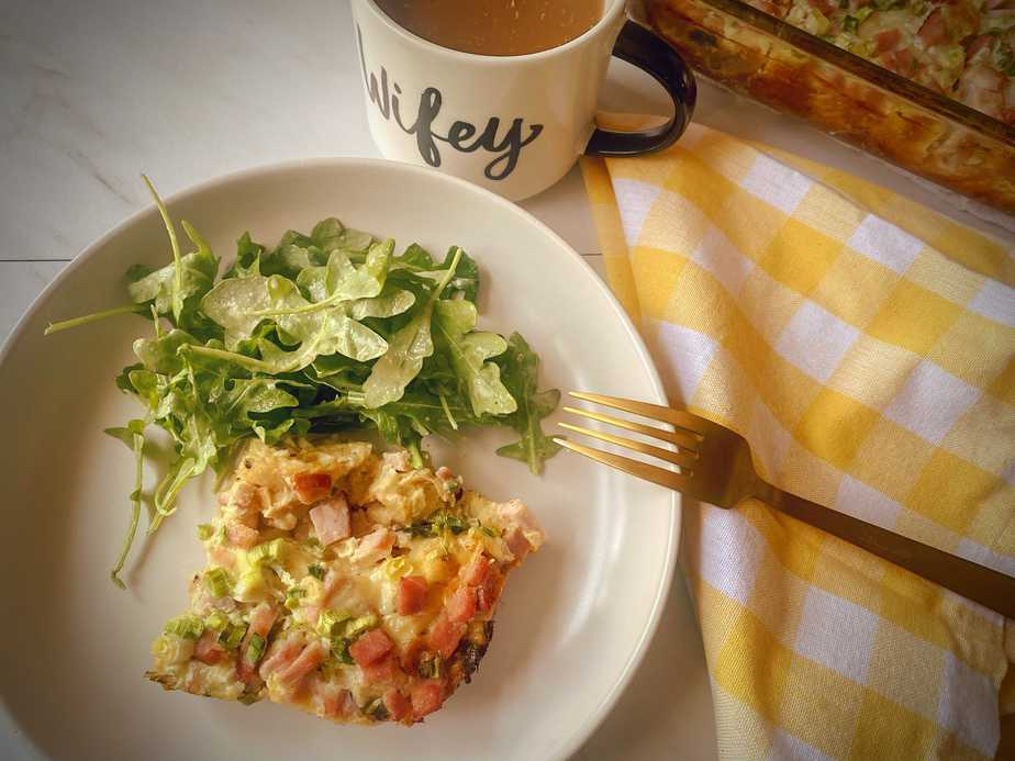 ham and swiss strata slice on a white plate with a green salad, gold fork, cup of coffee and breakfast casserole dish in the background
