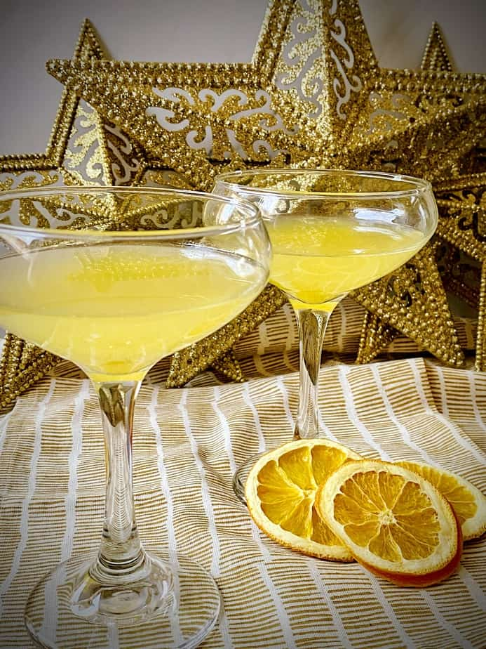 abbey cocktails in two coupe glasses with sparkling stars in the background and three orange slices