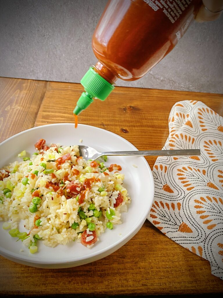 action shot of sriracha being drizzled onto a bowl of breakfast fried rice