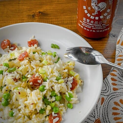 breakfast fried rice with chinese sausage plated in a white pasta bowl with a bottle of sriracha in the back ground and a silver spork with a orange, black and white patterned napkin