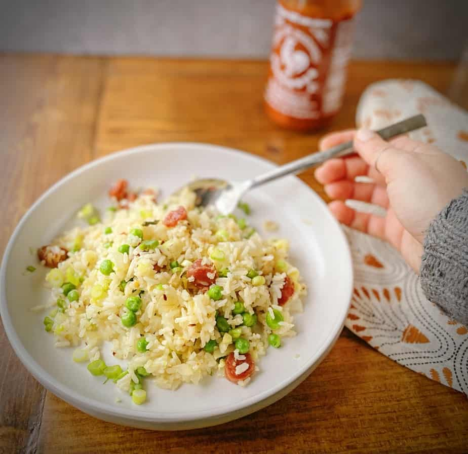 hand holding a spork to take a bite of breakfast fried rice with chinese sausage