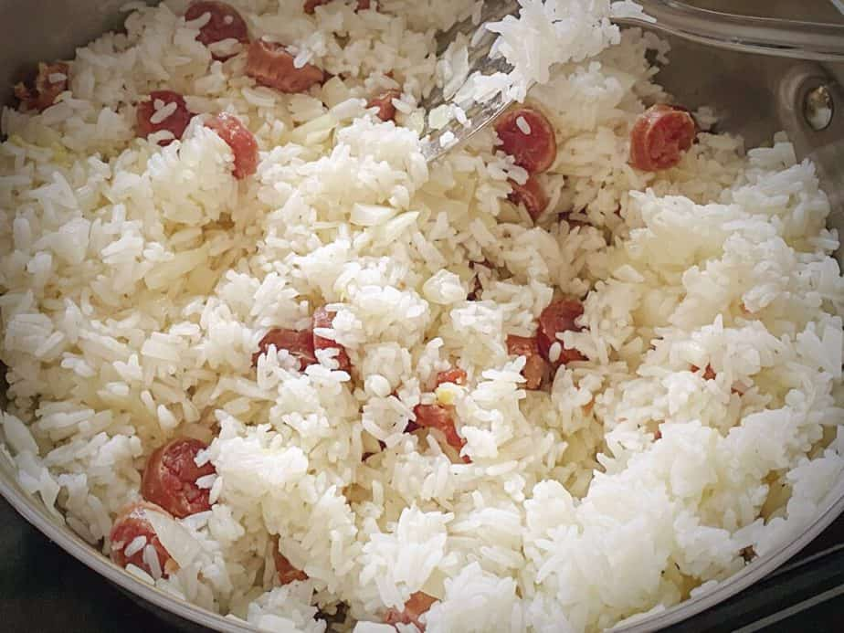 rice, onions and Chinese sausage in a sauté pan
