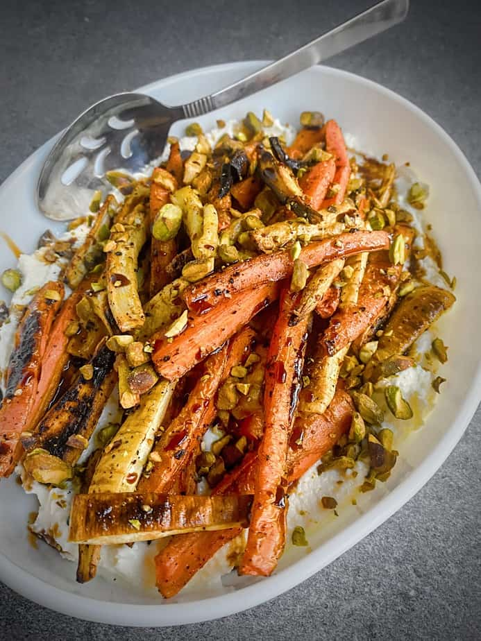 sumac roasted carrots and parsnips on a bed of whipped feta topped with chopped pistachios and a drizzle of pomegranate molasses in a white oval plate