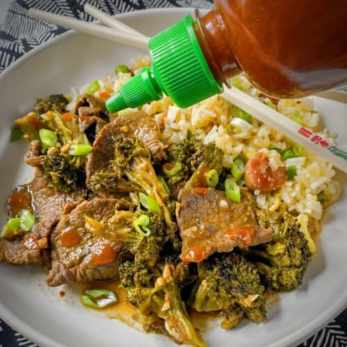 bottle of sriracha being drizzled onto completed plate of broccoli beef with fried rice