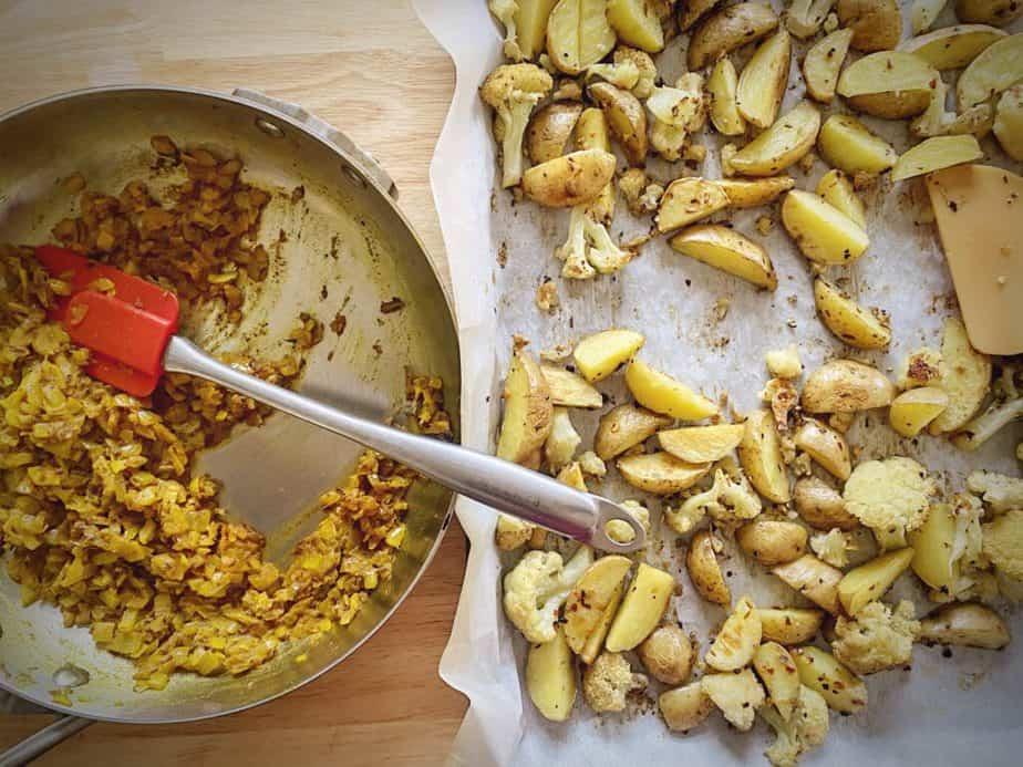 aloo gobi sauce in sauté pan next to sheet pan of roasted cauliflower and potatoes