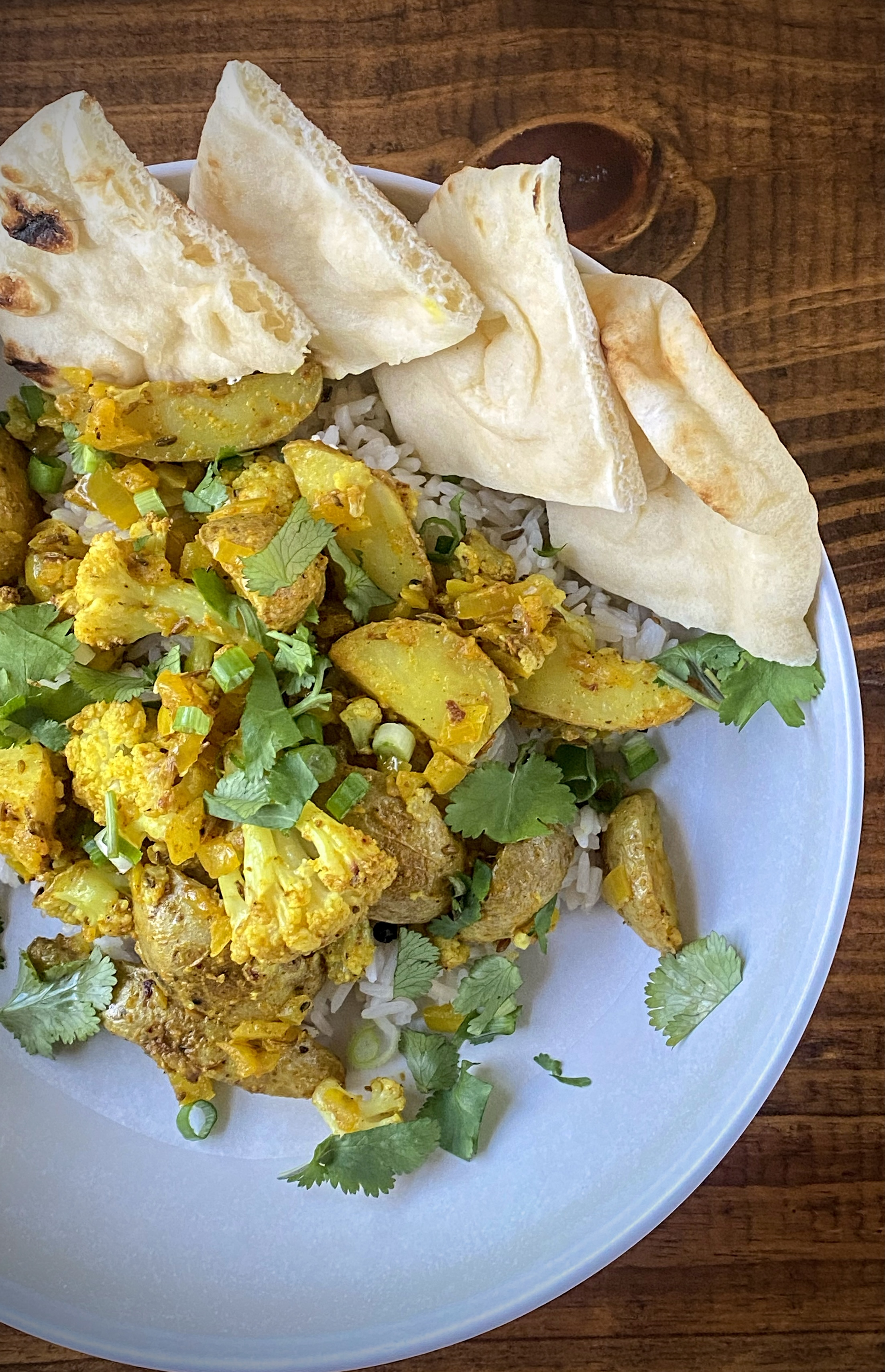 aloo gobi over cumin rice with sliced naan in a white pasta bowl on a wooden table