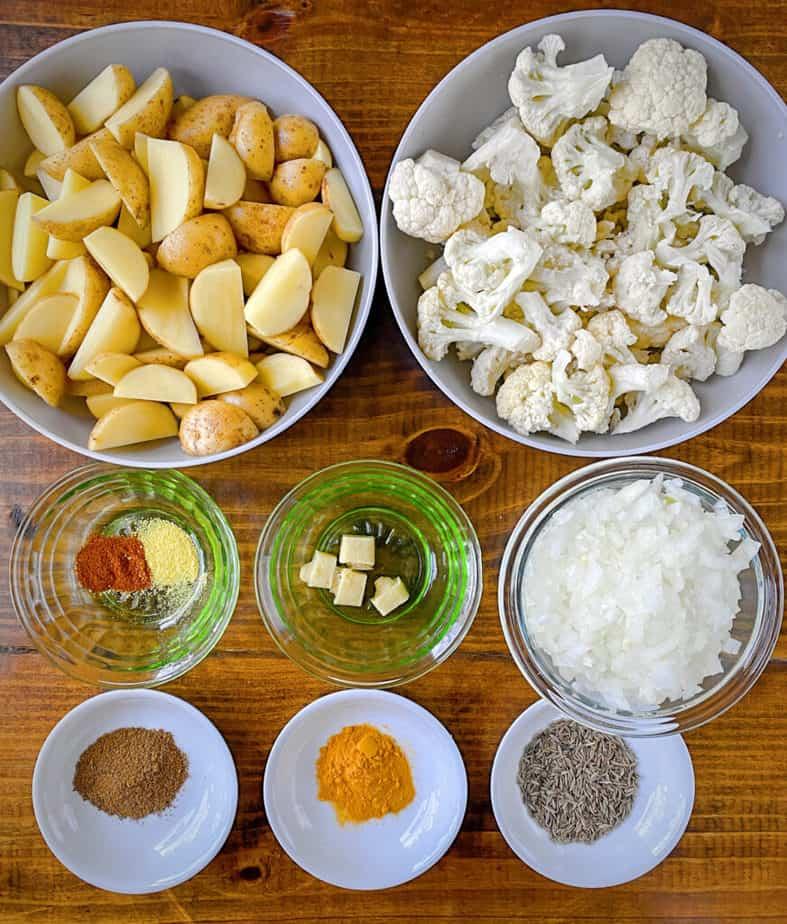 mise en place for aloo gobi - sliced potatoes, cauliflower florets, ginger, minced onion, asafoetida, chili powder, turmeric, cumin seeds and garam masala