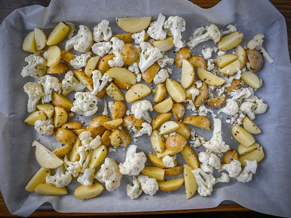 unroasted cauliflower and potatoes on a parchment lined sheet pan with spices and oil