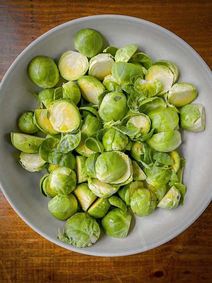prepared halved brussels sprouts in a grey bowl with a glug of olive oil