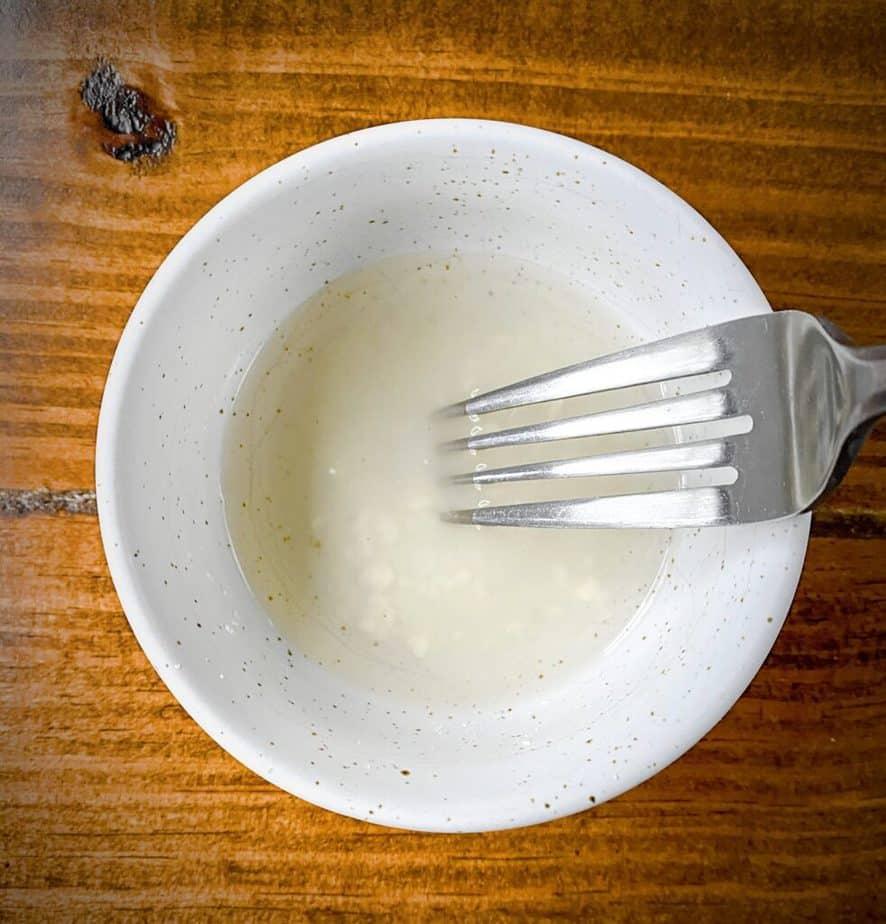 fork stirring together vinegar and cornstarch into a slurry