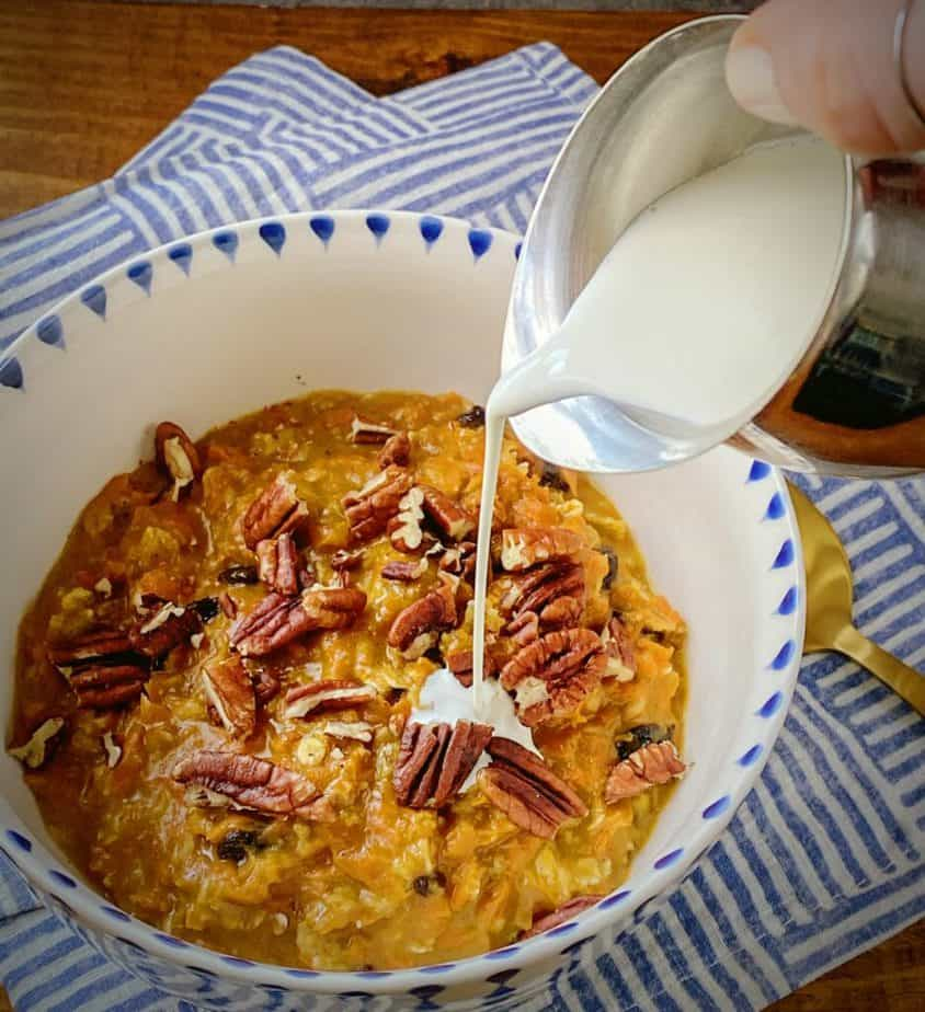 hand holding a silver creamer dish pouring heavy cream onto bowl of carrot cake oatmeal
