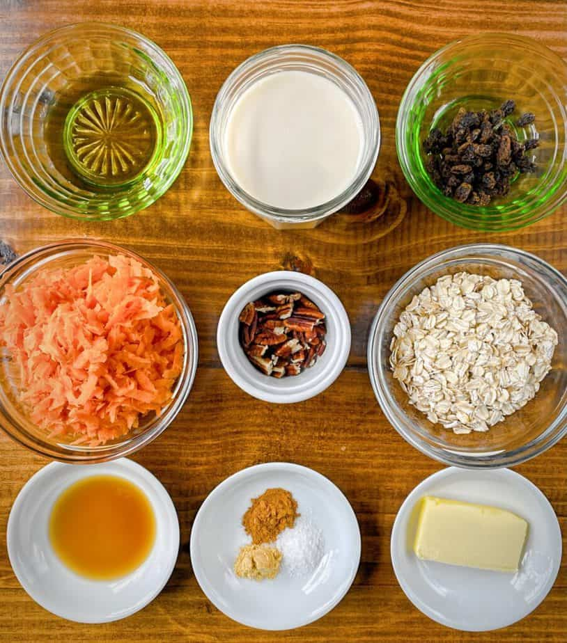 mise en place for carrot cake oatmeal recipes - agave, soy milk, raisins, shredded carrot, rolled oats, vanilla, ground cinnamon, ground ginger, kosher salt and butter all in small bowls