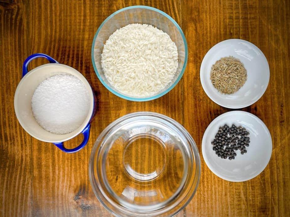 mise en place for cumin rice - salt, water, jasmine rice, cumin seeds and peppercorns