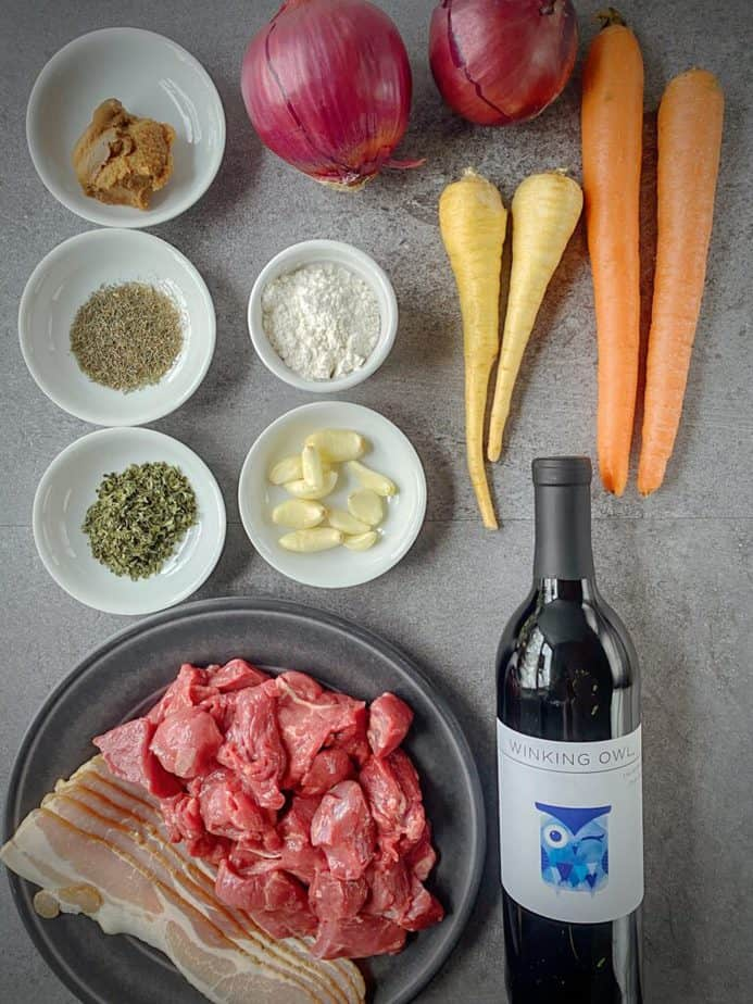 mise en place for instant pot beef stew - 2 red onions, 2 carrots, 2 parsnips, miso paste, spices, flour, garlich, beef stew meat and bottle of red wine