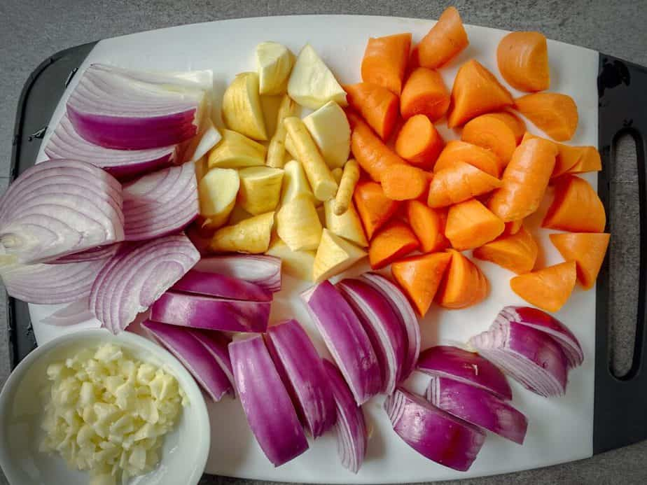 overhead shot of prepared carrots, parsnips, red onion and garlic for beef stew