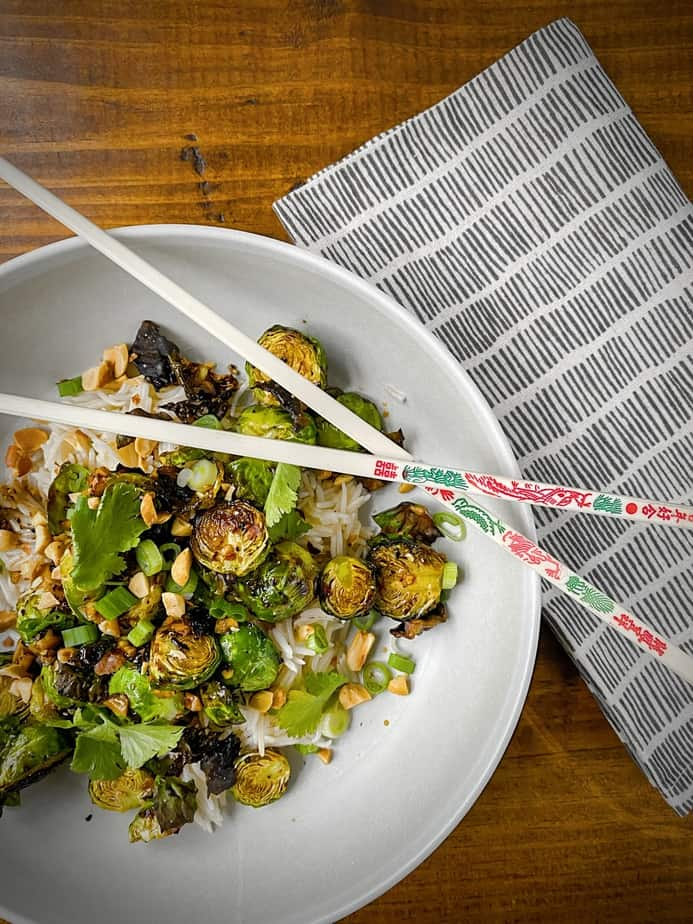 kung pao brussels sprouts in white pasta bowl on brown wood table with a black etched linen and embellished chopsticks