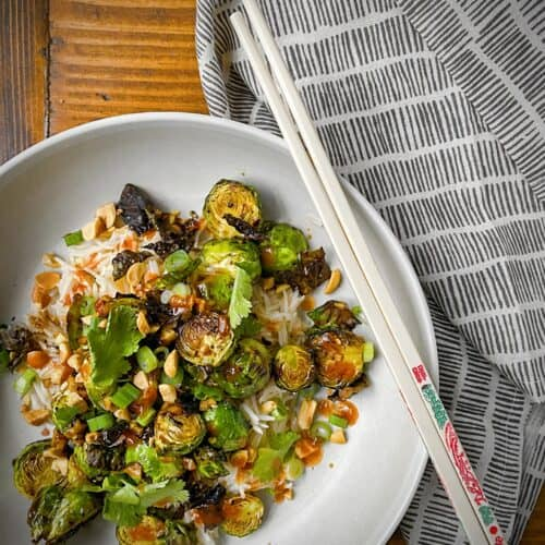 kung pao brussels sprouts in white pasta bowl over jasmine rice