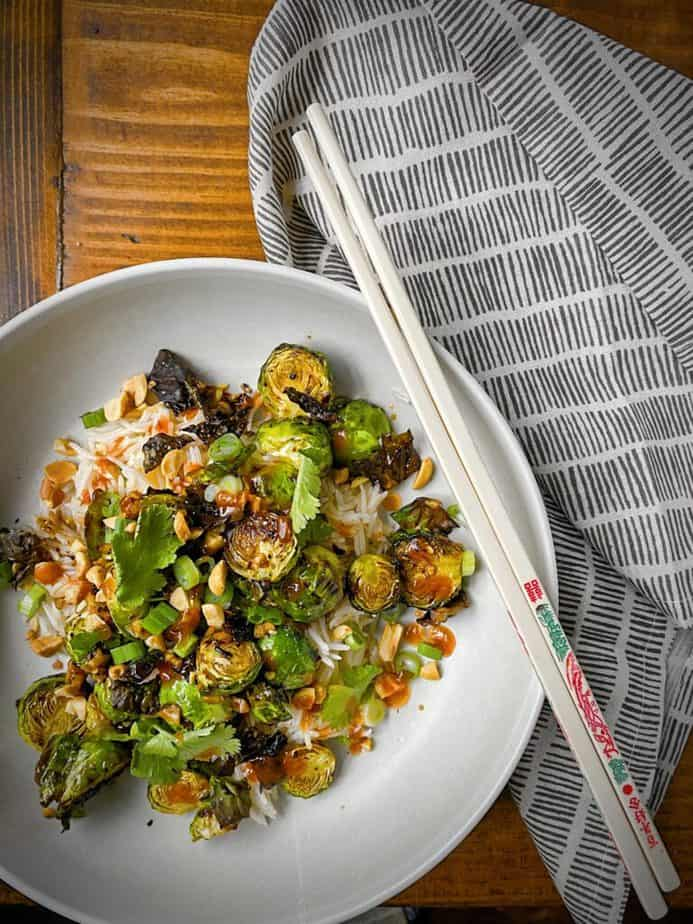 overhead shot of kung pao brussels sprouts plated over jasmine rice in a white pasta bowl and garnished with cilantro, green onions and peanuts