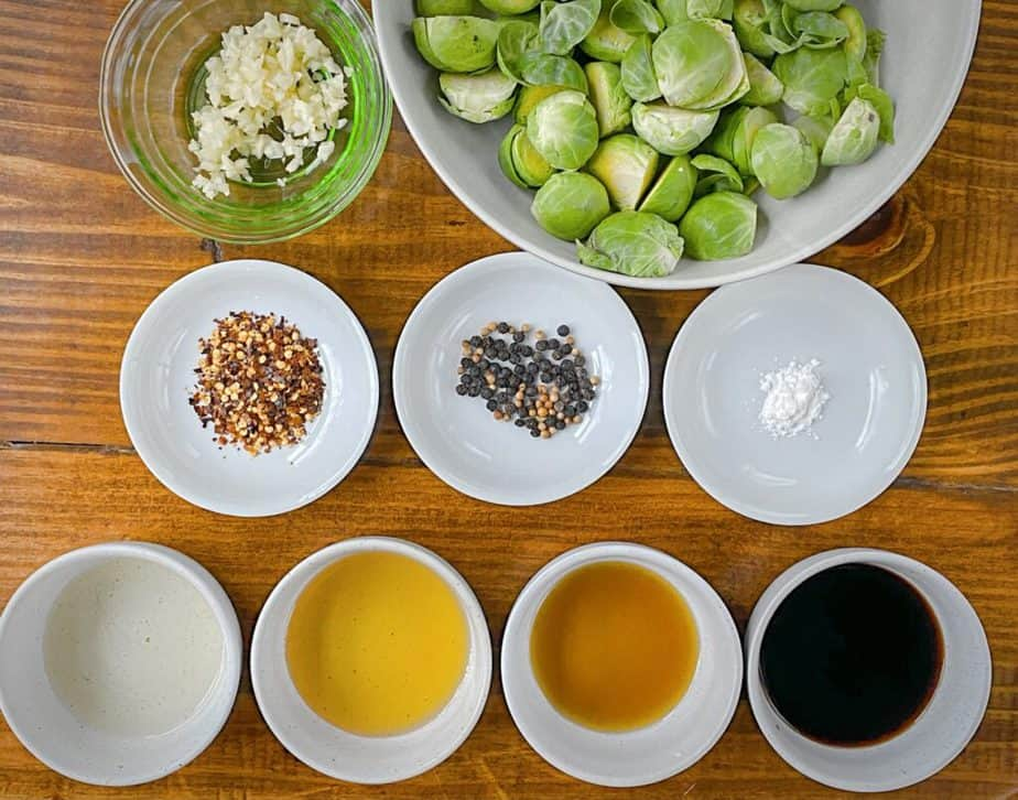 mise en place for kung pao brussels sprouts - minced garlic, halved brussels, red pepper flakes, mix of peppercorns and coriander seeds, cornstarch, rice vinegar, agave, soy sauce and sesame oil