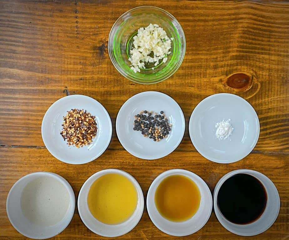 mise en place for kung pao sauce - minced garlic, red pepper flakes, peppercorns and coriander seeds, cornstarch, rice wine vinegar, agave, sesame oil and soy sauce