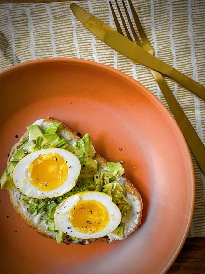 overhead shot of halved turmeric pickled egg on simple avocado toast on a terracotta plate with gold silverware