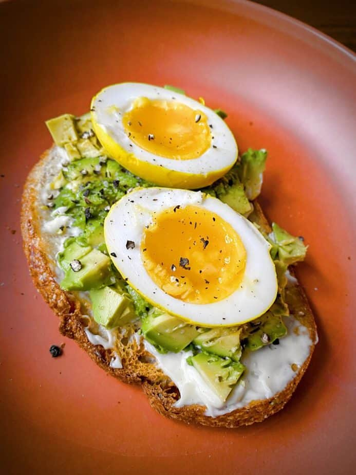 45 degree angle shot of halved turmeric pickled egg on avocado toast to show bright yellow exterior