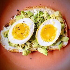 overhead close up shot of halved turmeric pickled egg on avocado toast