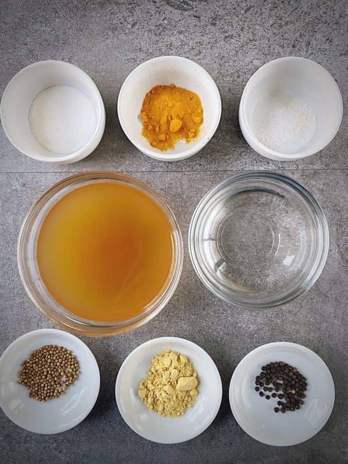 mise en place for turmeric pickled eggs brine - salt, turmeric, whole peppercorn, sugar, coriander seed, mustard powder, ACV, water