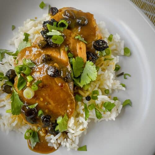 slices of roasted pork tenderloin with ginger raisin pan sauce over a bed of rice in a white bowl
