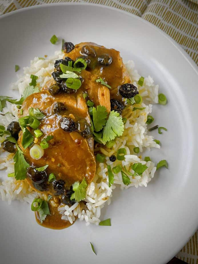 close up overhead shot of slices of roasted pork tenderloin with ginger raisin pan sauce over a bed of jasmine rice in a white pasta bowl with garnish of fresh cilantro and green onions